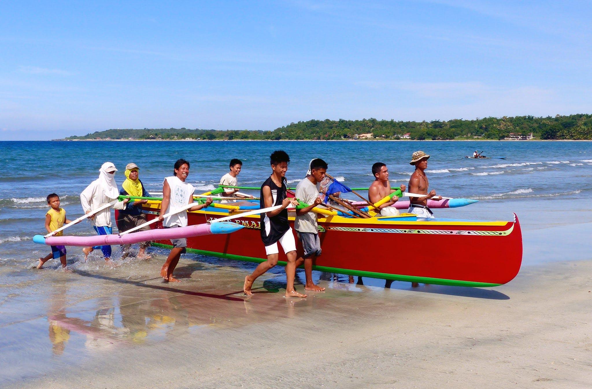 Fishers in Currimao Beach, Ilocos Norte, Philippines, hauling their boat ashore