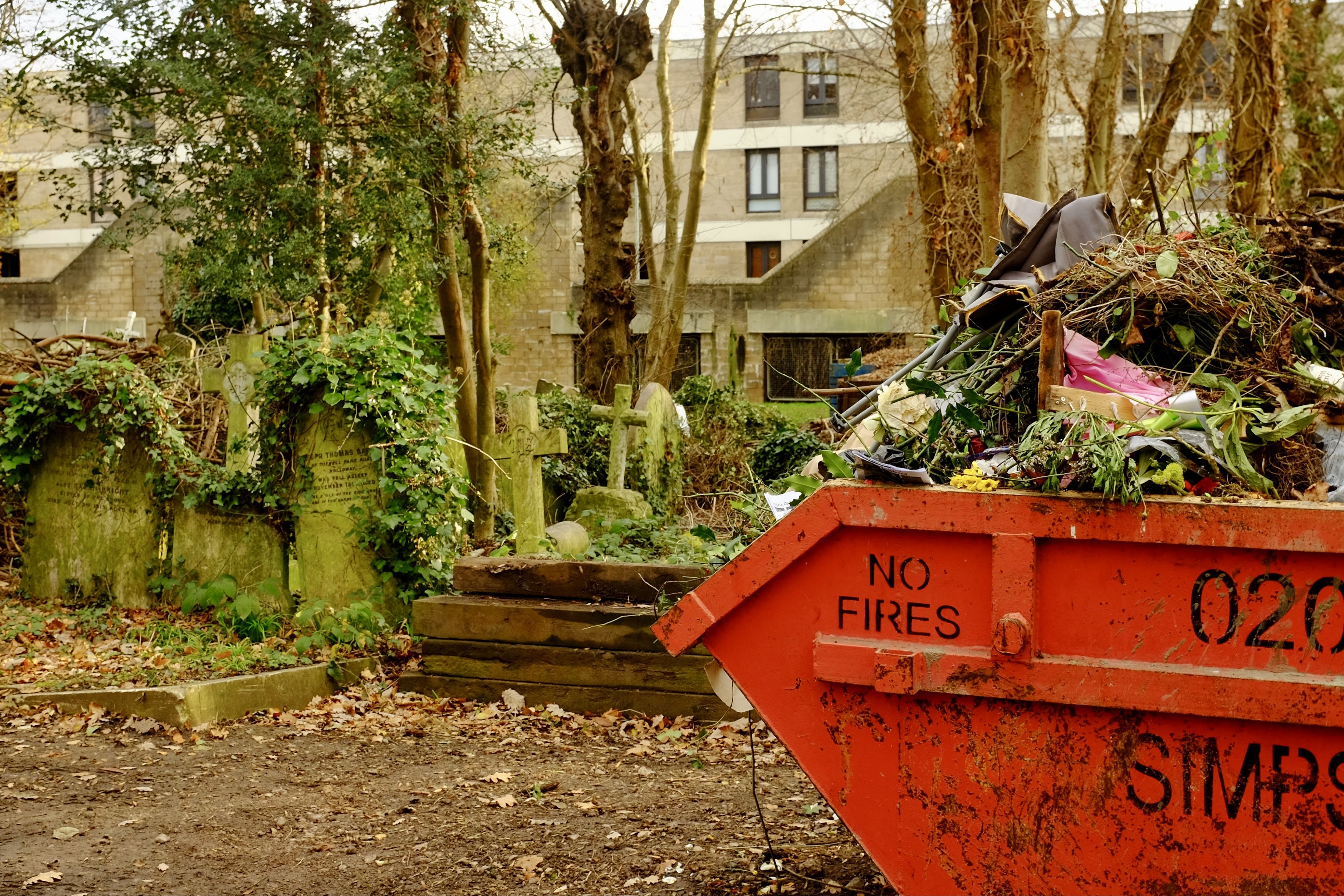 A large dumpster near a traditional cemetery