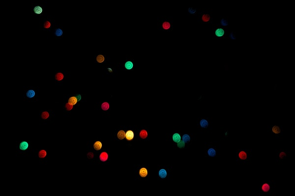 brightly colored green, red, blue, and yellow dots against a black background