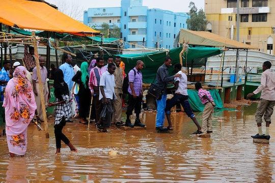 people wading through flooding in sudan