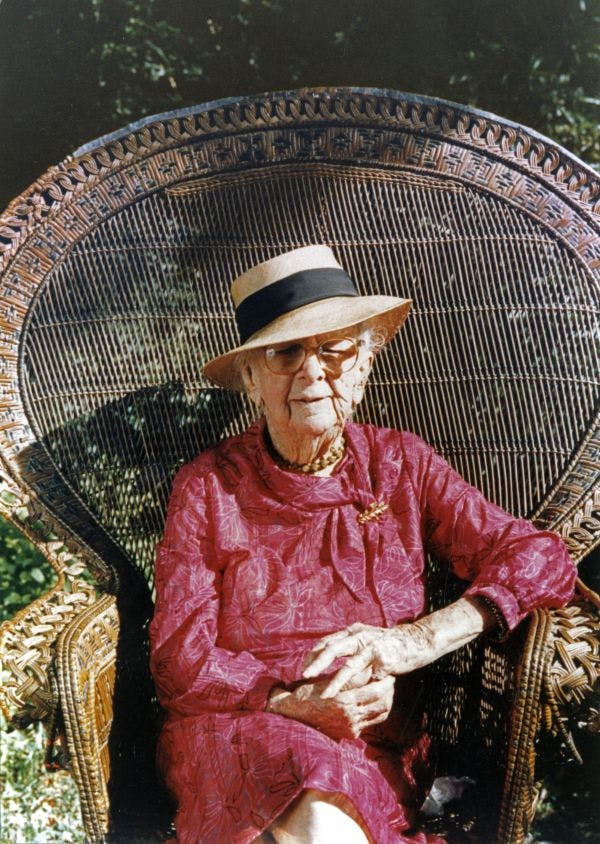 Marjory Stoneman Douglas, wearing a red dress and a brimmed sun hat, sitting in a high backed wicker chair.