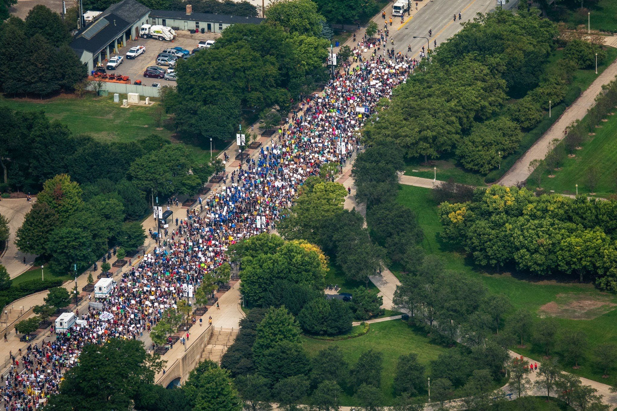 An aerial shot of a crowd of climate strikers marching down the street in Chicago, IL, USA.