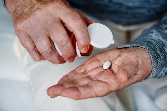 white hands holding one white, oval-shaped pill