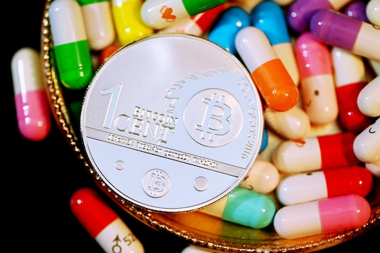 A Bitcoin on top of some pills