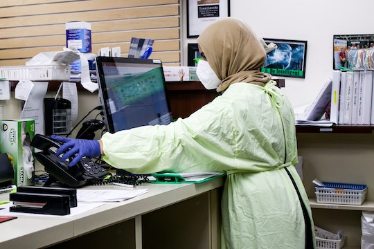 a woman wearing protective gear in a hospital working at a computer