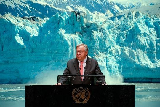 Antonio Guterres stands at a desk in front of a calving glacier
