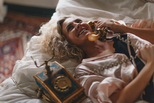 A woman laying on a bed talking on an old-timey rotary phone.