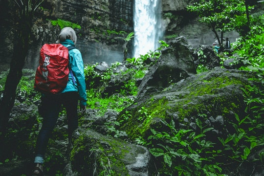 a woman wearing a hijab with a red backpack hiking to a waterfall