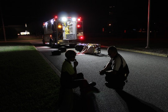 A paramedic talks to a patient on a darkened street next to an ambulance with its lights flashing.