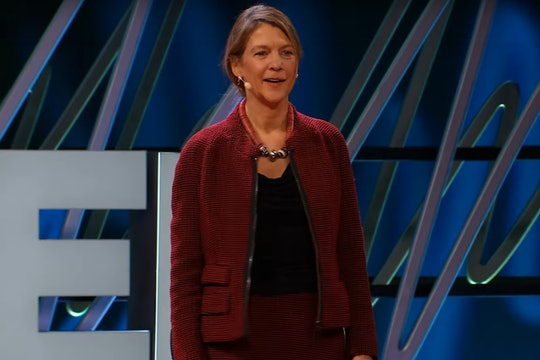 heidi larson, a woman wearing a red suit, standing on stage to give a talk