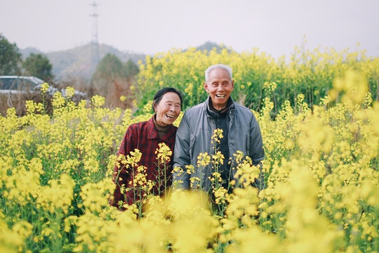 an older couple smiling and standing in a field of yellow flowers