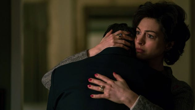 A still from the movie Dark Waters. Anne Hathaway playing Sarah Barlage hugs a young man.