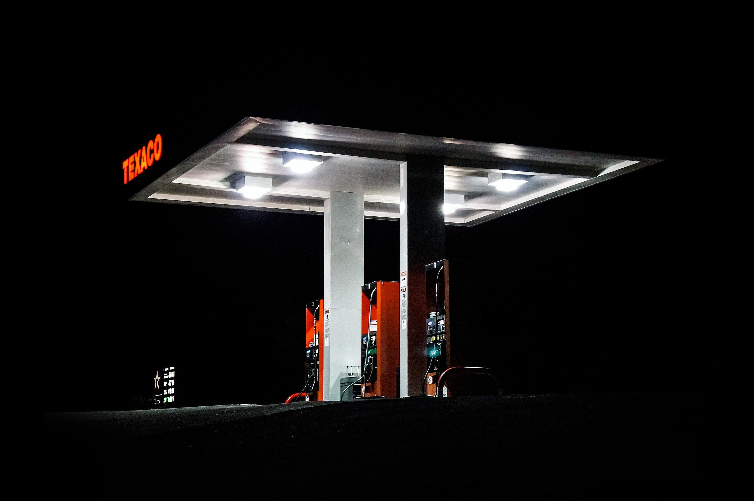 side angle photo of a texaco gas station taken at night