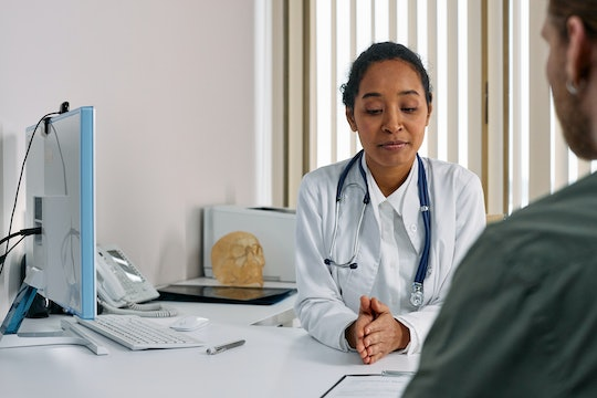 a woman doctor speaks with a man who is only partially visible