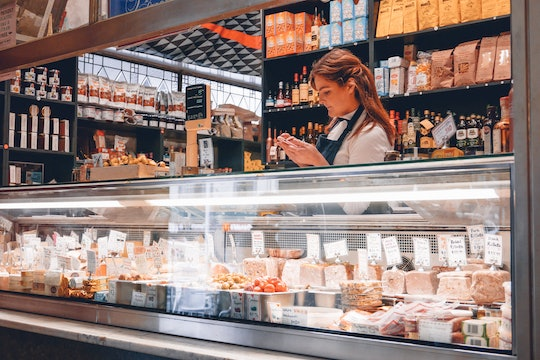 A clerk stands behind the counter of a deli stocked with meat and cheese.