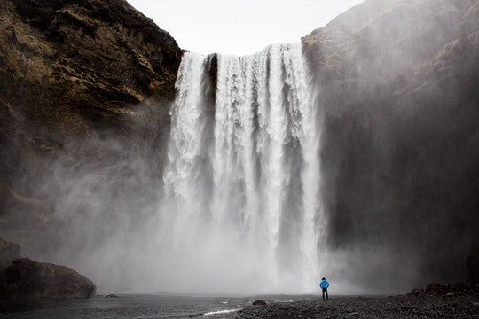 a person standing at the bottom of a huge waterfall