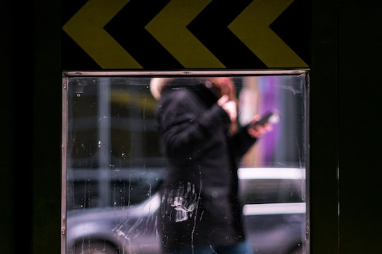 reflection of person looking at phone while walking