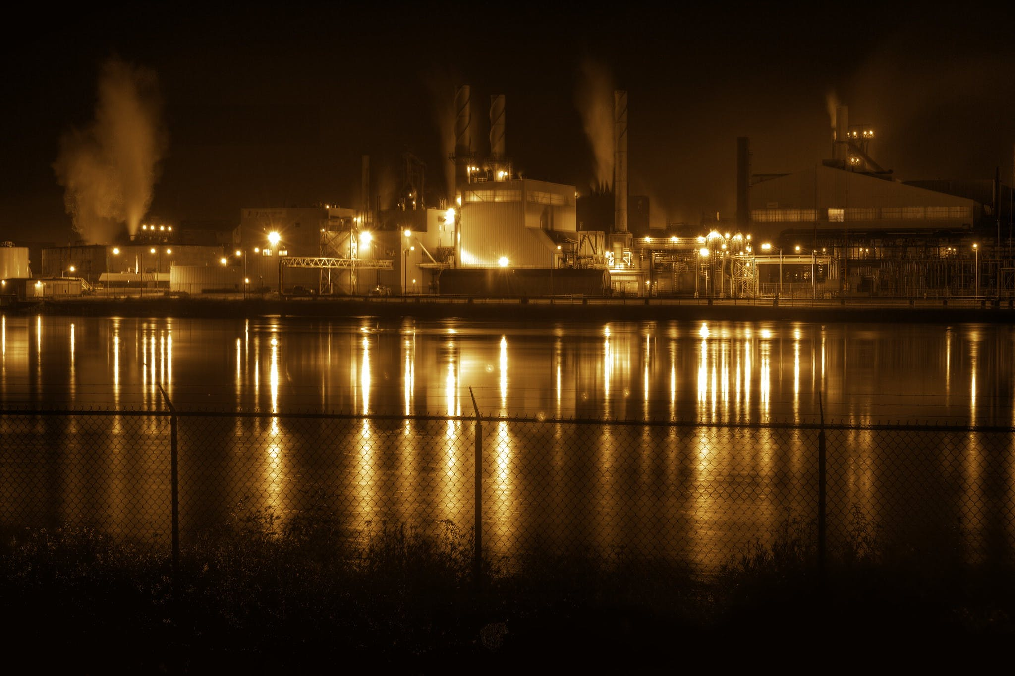 Essar Steel mill in Ontario, taking at night. A manufacturing plant lit up at night, seen from across a river.