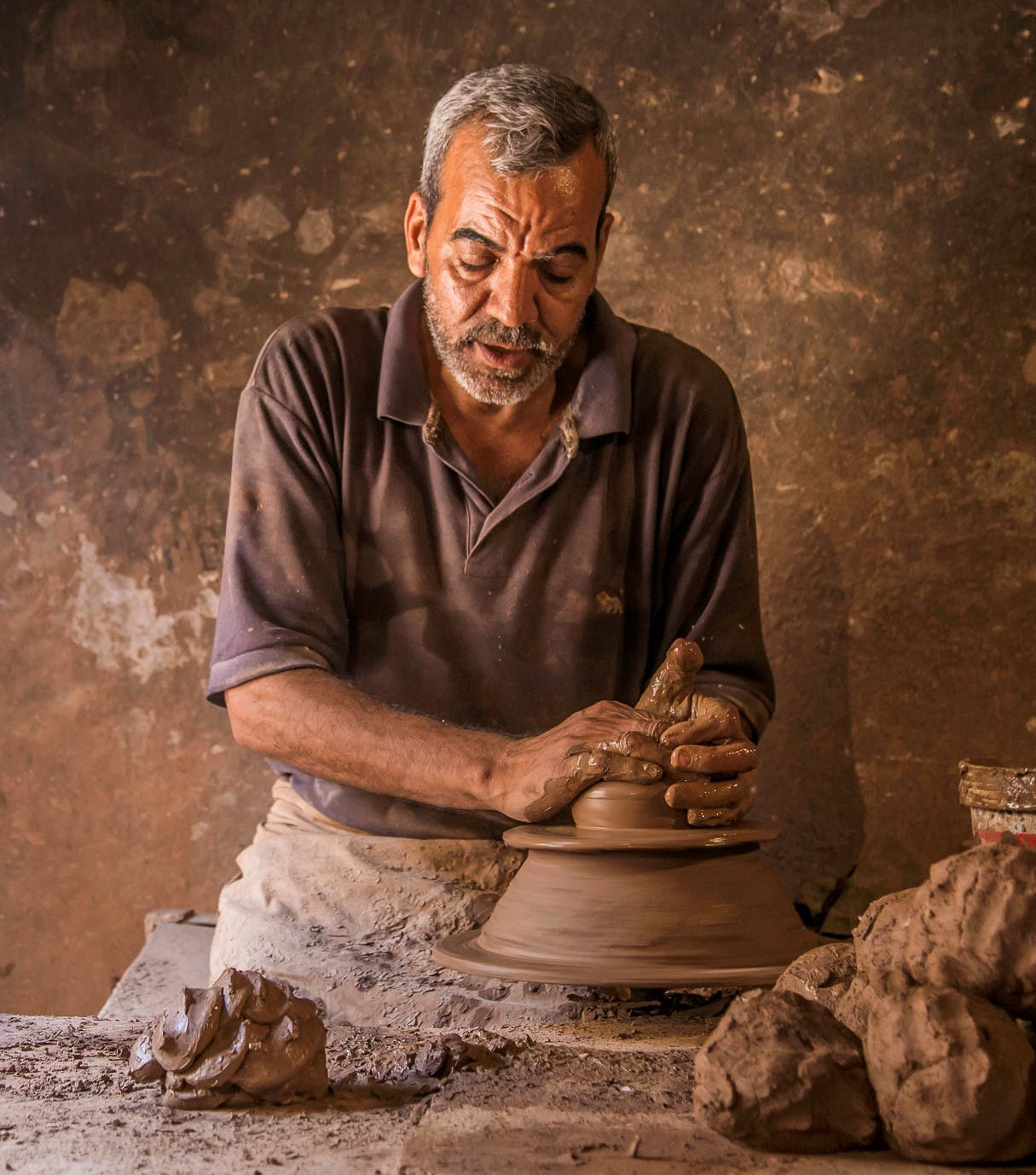 A man making a clay vase with his hands