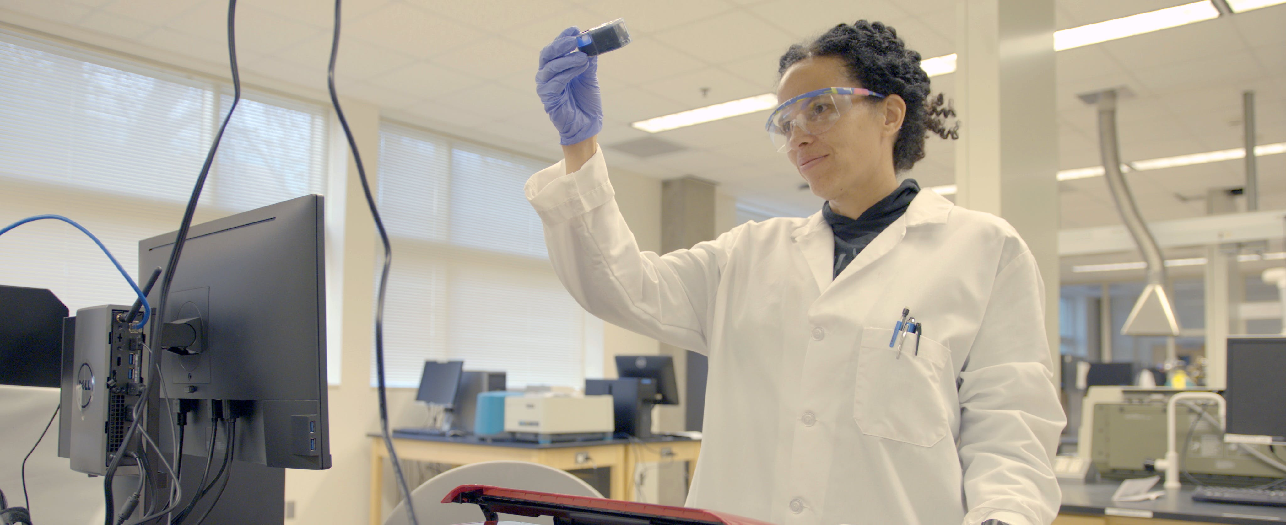 Chemist Raychelle Burks examines a sample while working in a lab