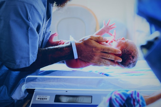 Newborn baby help by person in a hospital gown being weighed on a scale