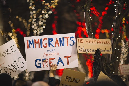 people holding signs that support immigration and refugees