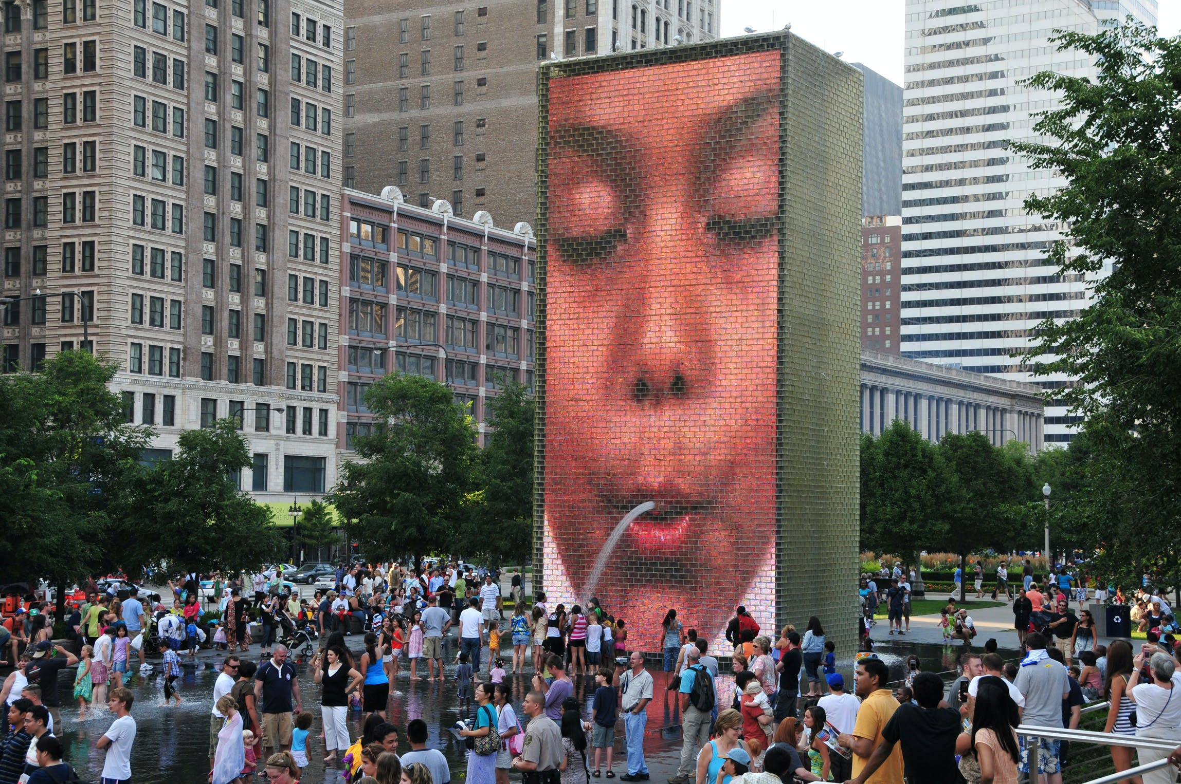 "A crowd gathers around Crown Fountain in Chicago's Millenium Park, where a fountain appears to ""spit"" water on visitors."
