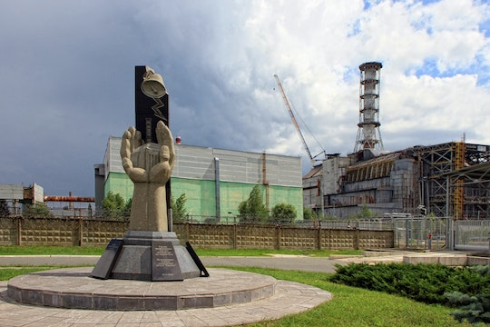 a statue in chernobyl with the wreckage of the plant in the background