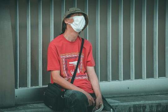 A man wearing a red shirt and a face mask leans back on a bench looking dejected