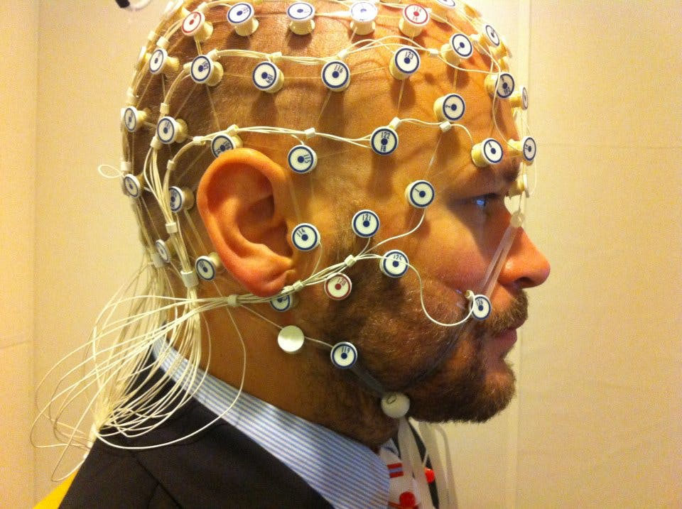 A man with EEG wires attached to his head.