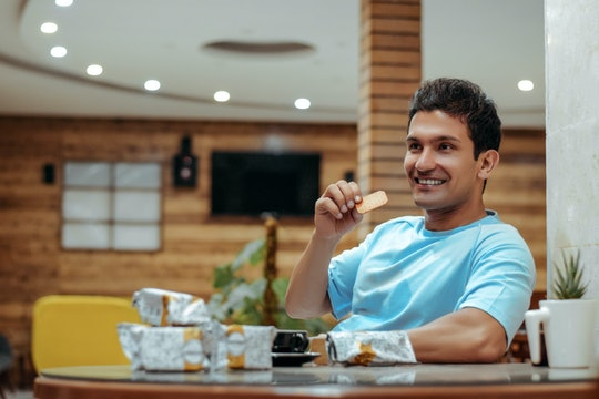 a man sitting at a table eating a biscuit
