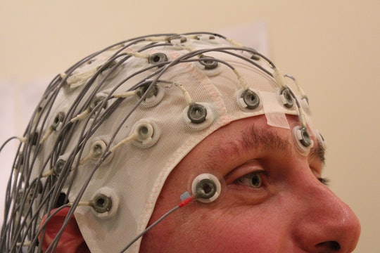 A man wearing an electroencephalography cap, with many wires protruding from a white nylon hat.
