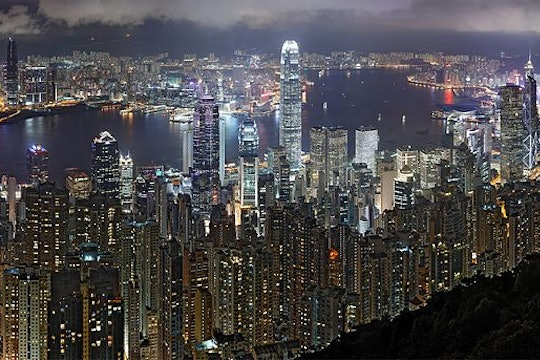 The skyline of Hong Kong, as seen at night. Many tall skyscrapers glow with artificial light.