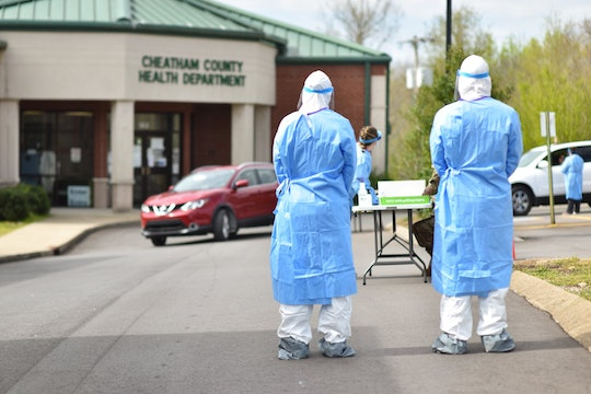 Two soldiers wearing personal protective equipment (PPE) stand waiting for a car in a drive-through coronavirus testing location.