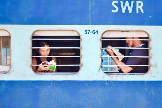 two people through the windows of a blue train