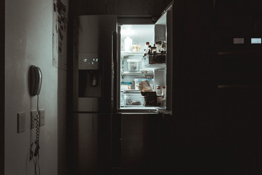 An open fridge or refrigerator in the dark.