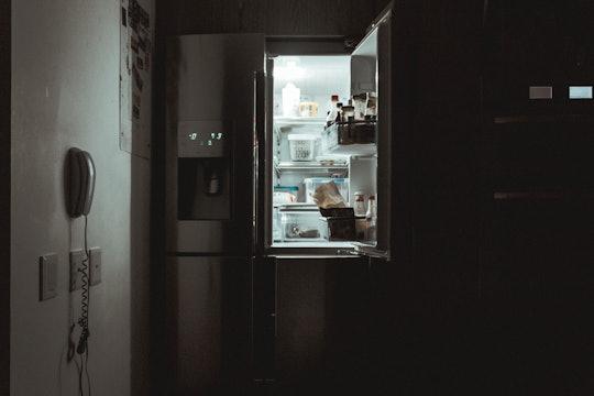 An open fridge or refrigerator in the dark.