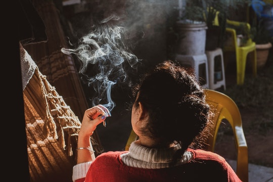 Woman smoking either tobacco or marijuana (weed).