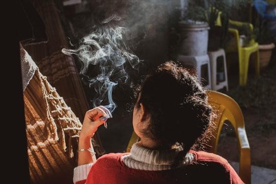 Woman smoking either tobacco or marijuana (weed).