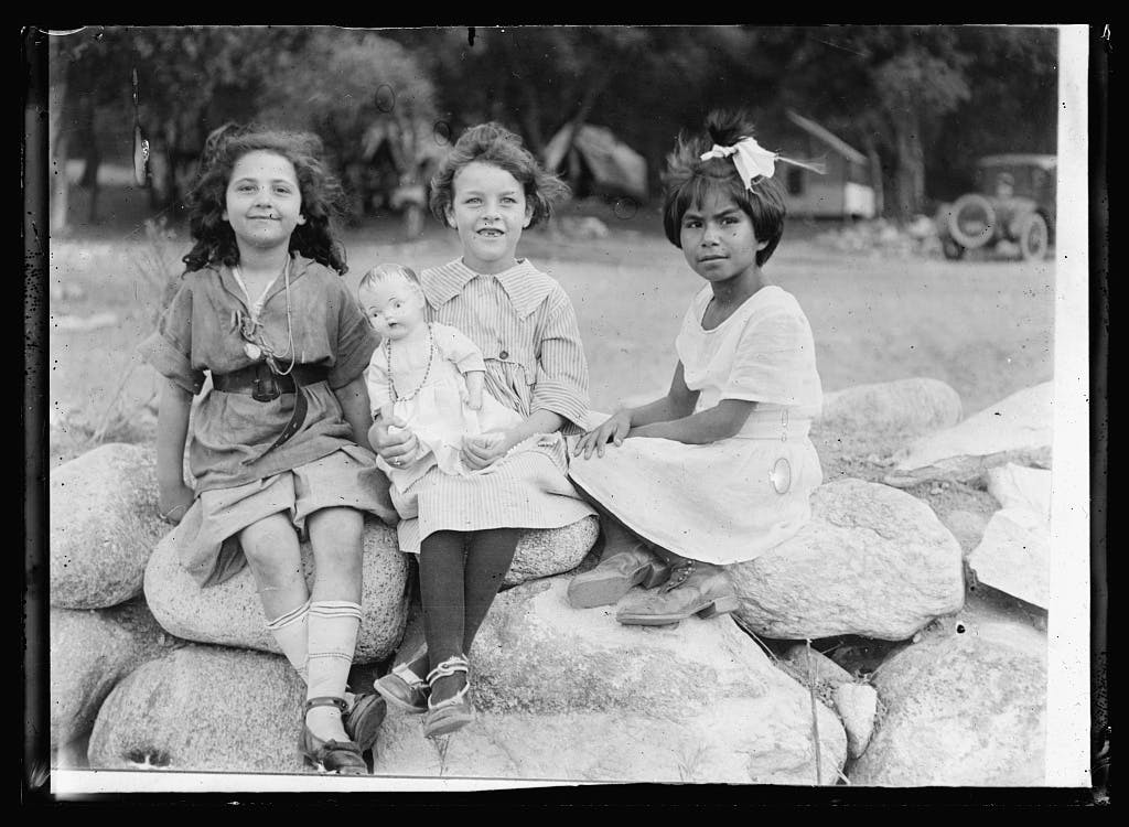 Three campers, 1920, sitting on a stone wall