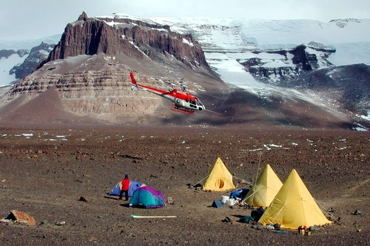 A helicopter prepares to land at Beacon Valley in the Dry Valleys of Antarctica.