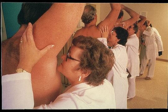 a line of women wearing lab coats smelling the armpits of a bunch of men