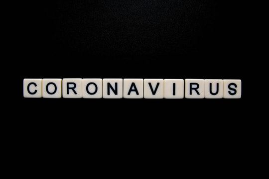 scrabble tiles on black background spelling coronavirus