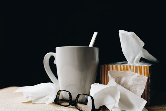 a table with a mug, glasses, and a tissue box