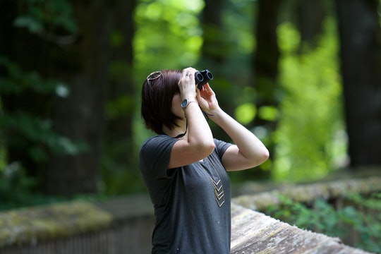 a woman standing outside looking through binoculars