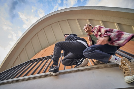 two guys climbing on a railing