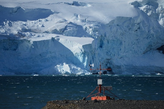 a weather station on a lake with a glacier in the background