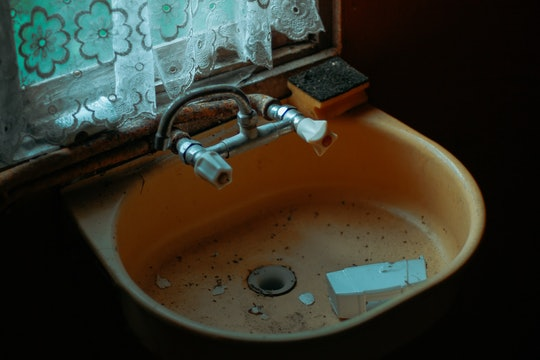 An old, dirty ceramic sink