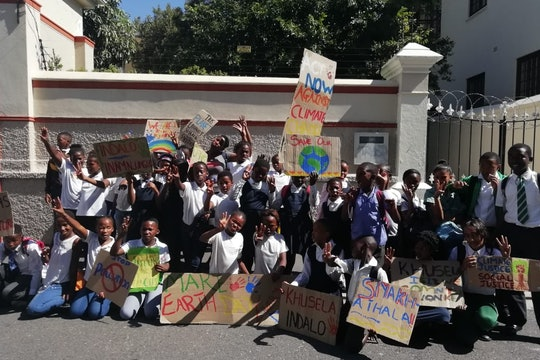 A group of young climate strikers gather with signs in Cape Town, South Africa.