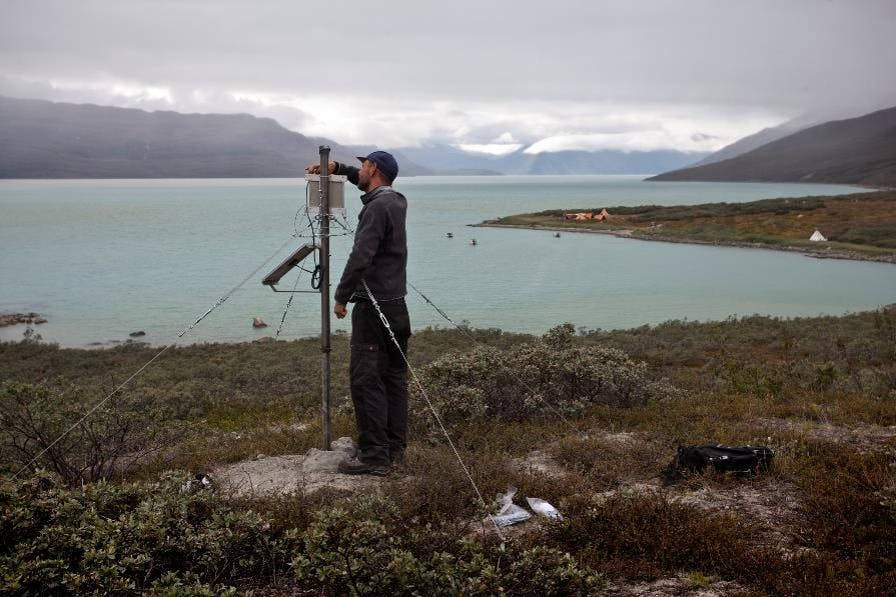 Next to a lake ringed by mountains, a scientist sets up a surveying probe.